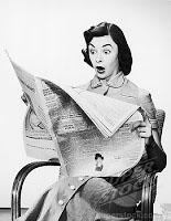 Surprised woman reading newspaper